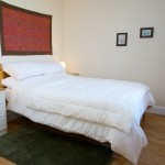 Image of bedroom showing double bed with white bed linen, bedside drawers and mirror in Cosaig Self-Catering Innerleithen