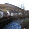 Photograph taken from the Cuddy Bridge in Innerleithen, Scottish Borders, with the Leithen Water, some cottages and Lee Pen in the background