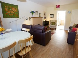 Photo of living room showing dining table, looking through to kitchen at Cosaig Self-Catering Innerleithen